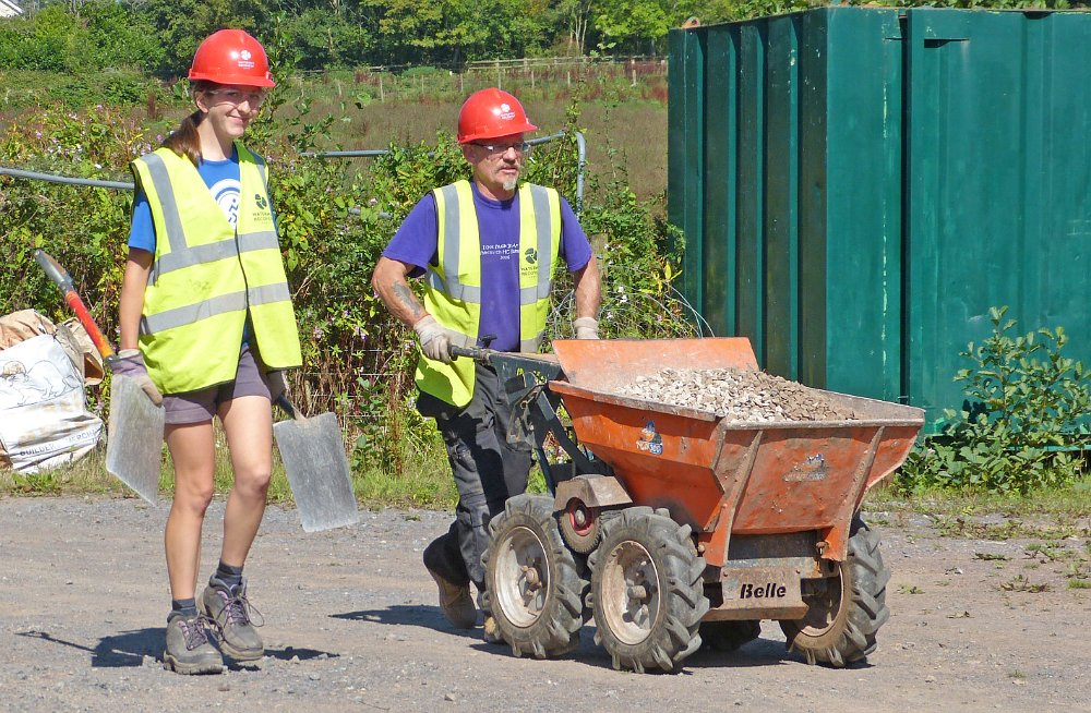 Two volunteers working on the Waterway Recovery Group canal camp, one steering a motorised wheelbarrow