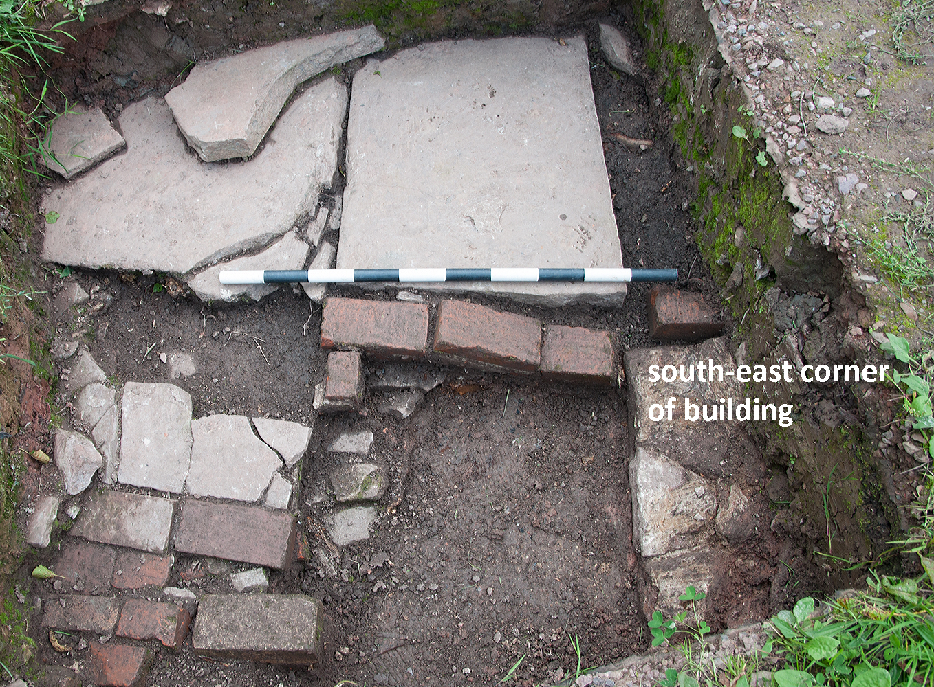 Flagstones and bricks laid to create a level surface outside the cottage wall.